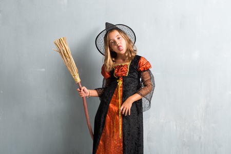 Little girl dressed as a witch and holding a broom for halloween holidays taking out her tongue