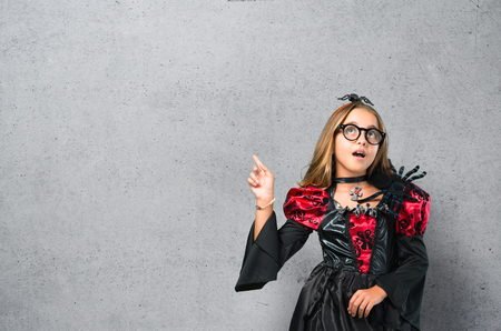 Blonde child dressed as a vampire for halloween holidays standing and thinking an idea on textured background Stock Photo