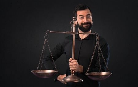 Handsome man with beard holding a balance on black background