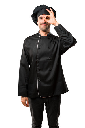 Chef man In black uniform makes funny and crazy face emotion on isolated white background Stock Photo