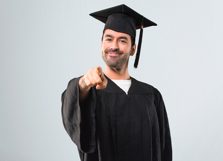 Man on his graduation day University points finger at you with a confident expression on grey background