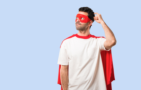 Superhero man with mask and red cape having doubts and with confuse face expression while scratching head on isolated blue background