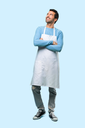 Full body of Man wearing an apron stand and looking up while smiling on blue background