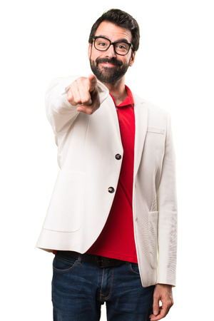 Brunette man with glasses pointing to the front on white background