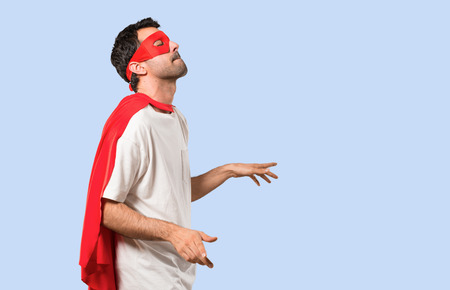 Superhero man with mask and red cape enjoy dancing while listening to music at a party on isolated blue background Stock Photo