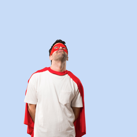 Superhero man with mask and red cape stand and looking up with serious face on isolated blue background