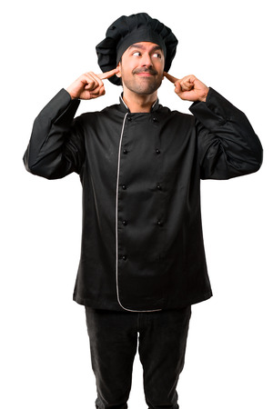 Chef man In black uniform covering both ears with hands on isolated white background