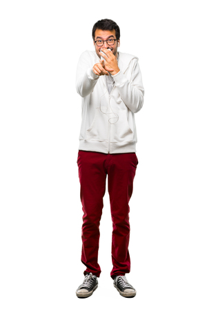 A full-length shot of a Man with glasses and listening music pointing with finger at someone and laughing a lot while covering mouth on white background Stock Photo