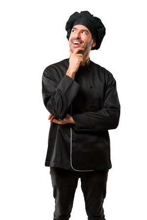 Chef man In black uniform standing and thinking an idea on isolated white background