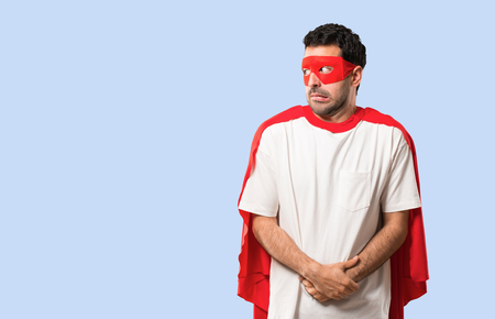 Superhero man with mask and red cape is a little bit nervous and scared pressing the teeth on isolated blue background