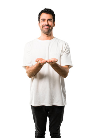 Young man with white shirt holding copyspace imaginary on the palm to insert an ad on isolated white background
