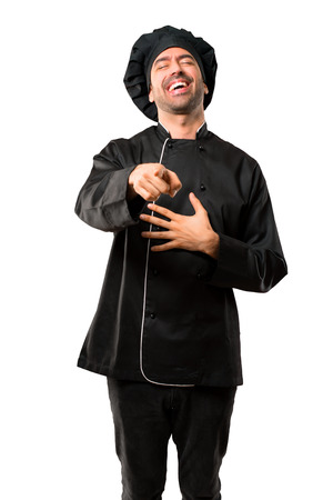 Chef man In black uniform pointing with finger at someone and laughing a lot on isolated white background