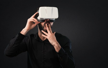 Handsome man with beard using VR glasses on black background Stock Photo