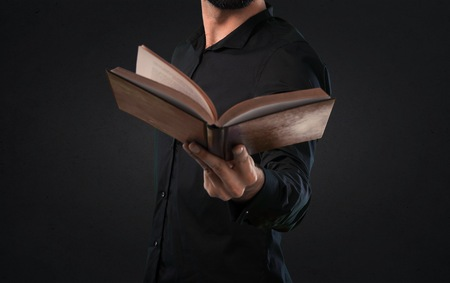 Handsome man with beard reading a book on black background