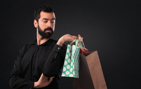 Handsome man with beard with shopping bag on black background