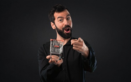 Handsome man with beard holding a supermarket cart toy on black background