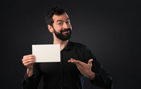 Handsome man with beard holding an empty placard on black background