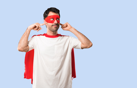 Superhero man with mask and red cape covering both ears with hands on isolated blue background