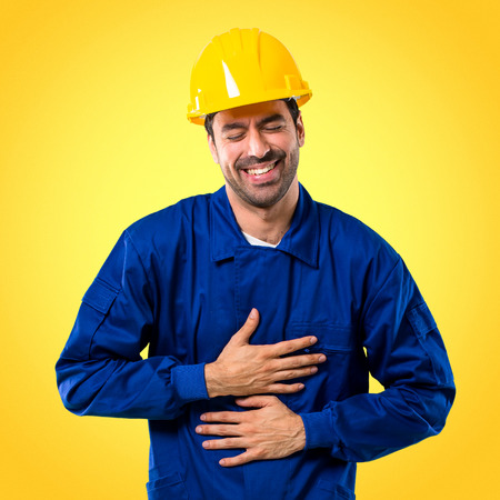 Young workman with helmet smiling a lot while putting hands on chest on yellow background