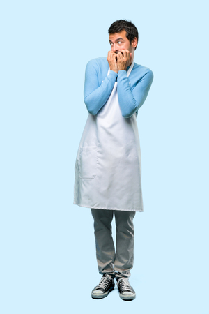 Full body of Man wearing an apron is a little bit nervous and scared putting hands to mouth on blue background