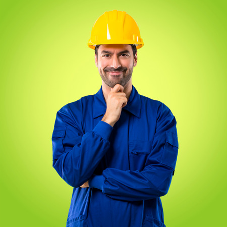 Young workman with helmet smiling and looking to the front with confident face on green background