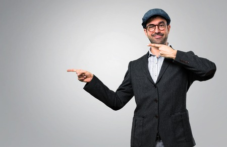 Handsome modern man with beret and glasses pointing finger to the side and presenting a product on grey background