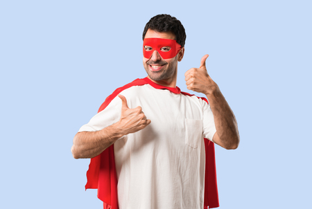 Superhero man with mask and red cape giving a thumbs up gesture and smiling because has had success on isolated blue background