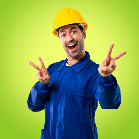 Young workman with helmet smiling and showing victory sign with both hands and with a cheerful face on green background