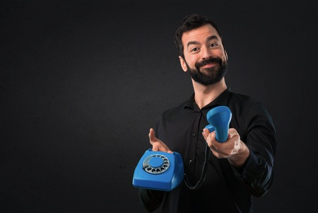 Handsome man with beard talking to vintage phone on black background