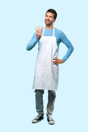 Full body of Man wearing an apron happy and counting three with fingers on blue background