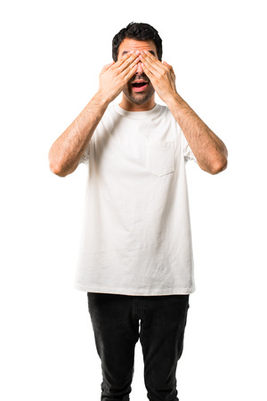Young man with white shirt covering eyes by hands. Surprised to see what is ahead on isolated white background