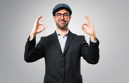 Handsome modern man with beret and glasses showing an ok sign with fingers on grey background