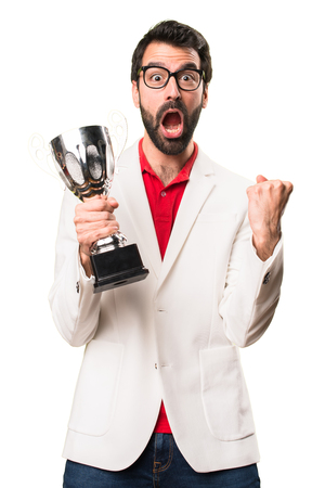 Happy Brunette man with glasses holding a trophy on white background
