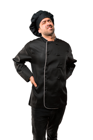 Chef man In black uniform unhappy and suffering from backache for having made an effort on isolated white background Stock Photo