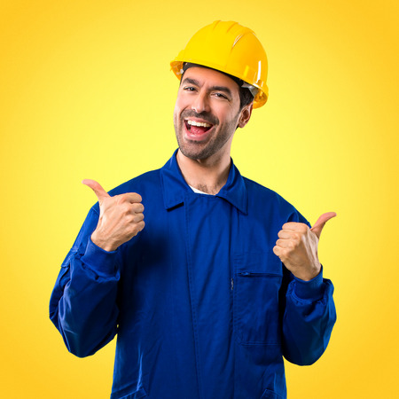 Young workman with helmet giving a thumbs up gesture with both hands and smiling. Cheerful expression on yellow background