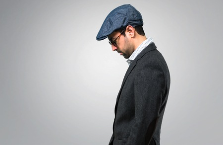 a3e69ea23dc21 Handsome modern man with beret and glasses in lateral position on grey  background Stock Photo