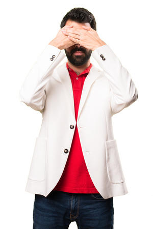 Brunette man with glasses covering his eyes on white background