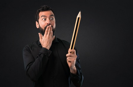 Handsome man with beard holding a big pencil on black background