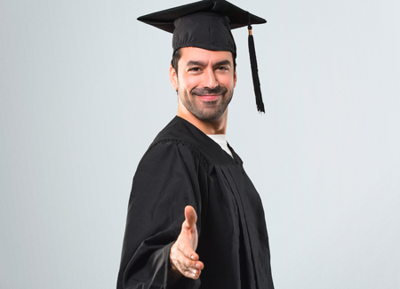 Man on his graduation day University handshaking after good deal on grey background