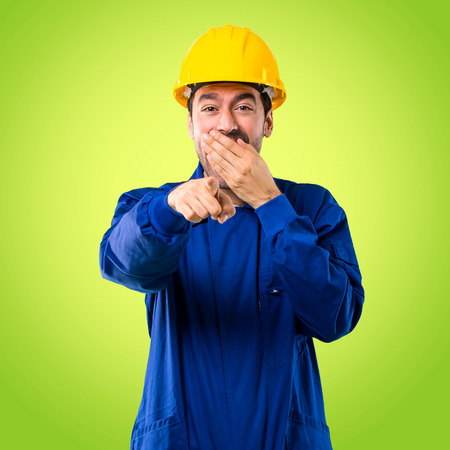 Young workman with helmet pointing with finger at someone and laughing a lot while covering mouth on green background