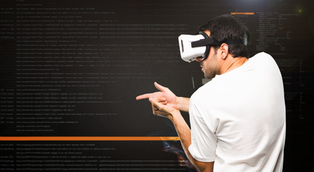 Man using VR glasses shooting with a virtual pistol inside the virtual reality mode