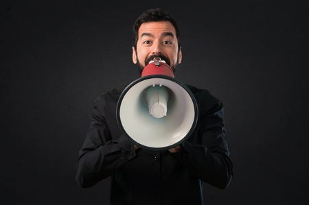 Handsome man with beard holding a megaphone on black background