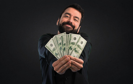 Handsome man with beard taking a lot of money on black background