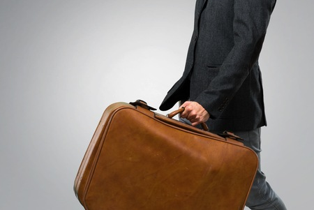 Handsome modern man with beret and glasses walking and holding a vintage briefcase on grey background