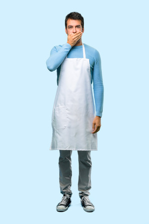 Full body of Man wearing an apron covering mouth with hands for saying something inappropriate. Can not speak on blue background