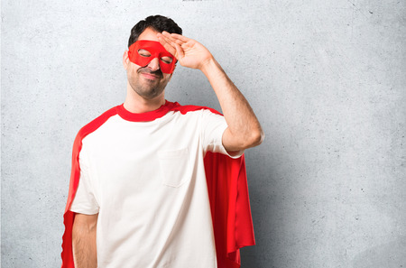 Superhero man with mask and red cape with tired and sick expression on textured grey background