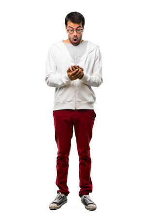 Full body of Man with glasses and listening music with surprise and shocked facial expression. Gaping because have just surprised with a gift on white background Stock Photo