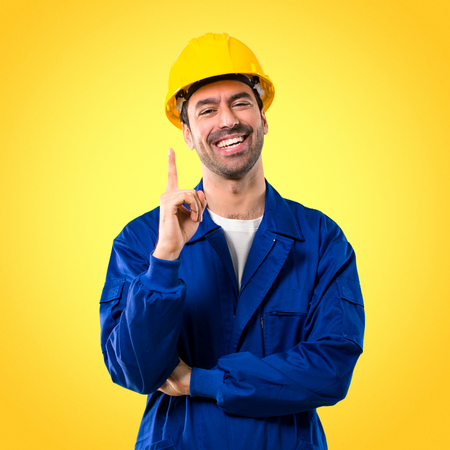 Young workman with helmet showing and lifting a finger in sign of the best on yellow background