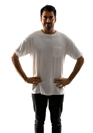 Young man with white shirt with arms at hip on isolated white background Stock Photo