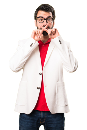 Brunette man with glasses making silence gesture on white background